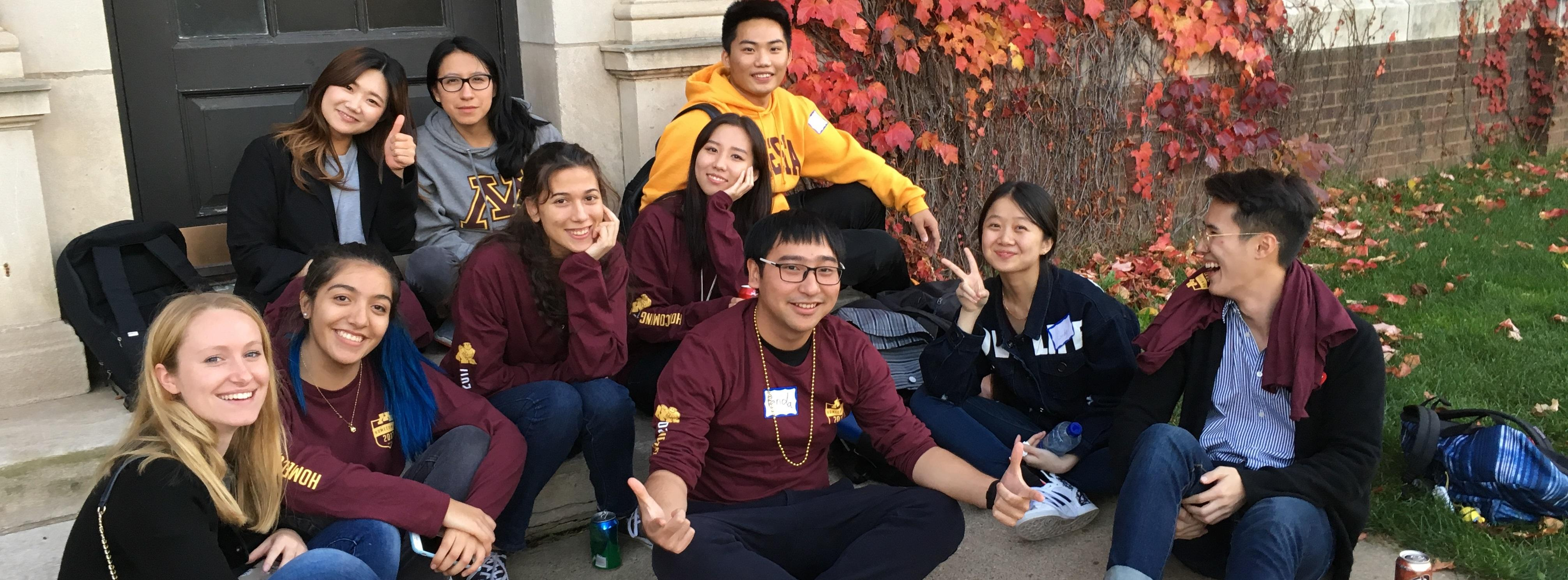 Students sitting on step outside at UMN Homecoming